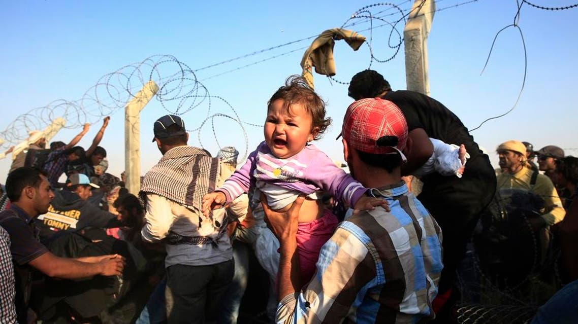 A Syrian refugee carries a baby after crossing over the broken border fence into Turkey from Syria in Akcakale, Sanliurfa province, southeastern Turkey, Sunday, June 14, 2015 | AP