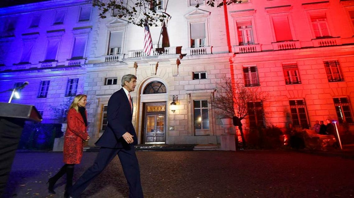 US Secretary of State John Kerry (C), next to US ambassador to France Jane D. Hartley, leaves after delivering a speech at the US embassy illuminated with the colors of the French national flag on November 16, 2015 in Paris. (Reuters)