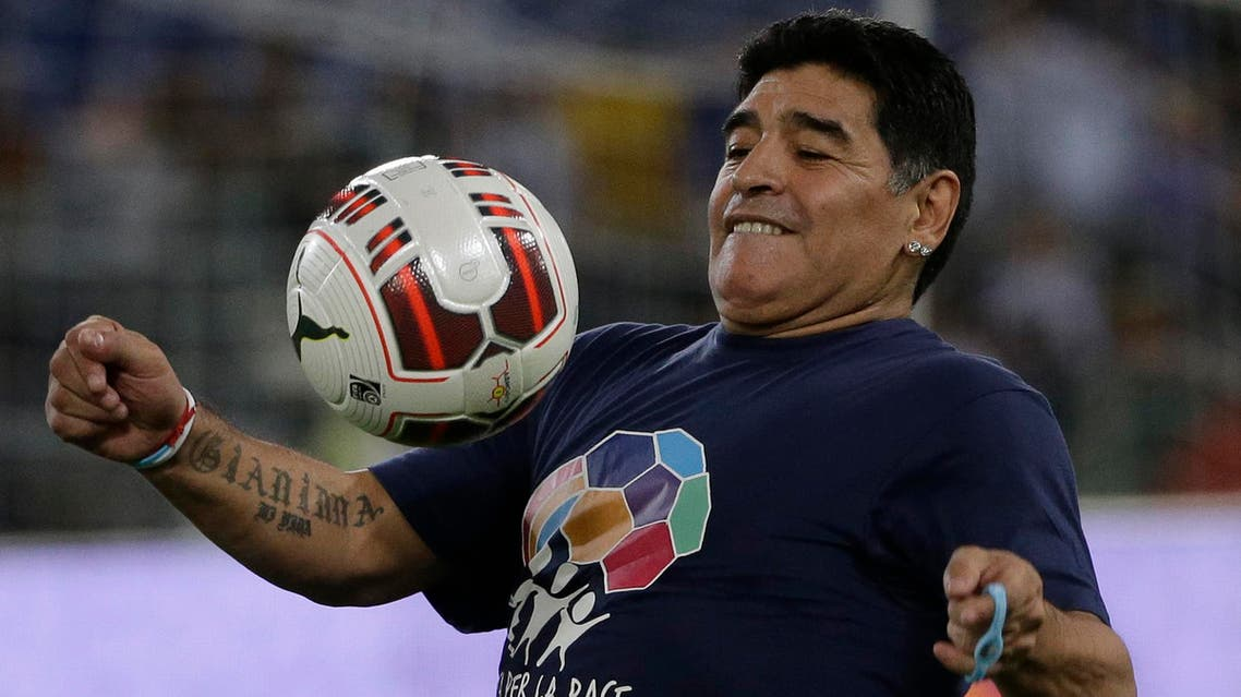Argentine soccer legend Diego Armando Maradona watches the ball as he warms up prior to the start of an inter-religious match for peace, supported by Pope Francis to promote the dialogue and peace among different religions, at Rome's Olympic Stadium, Monday, Sept. 1, 2014. (AP