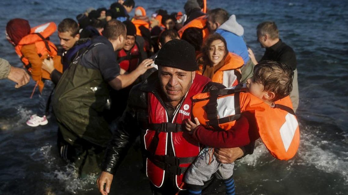 A migrant man holding a child reacts as refugees and migrants arrive on the Greek island of Lesbos. (File photo: Reuters)