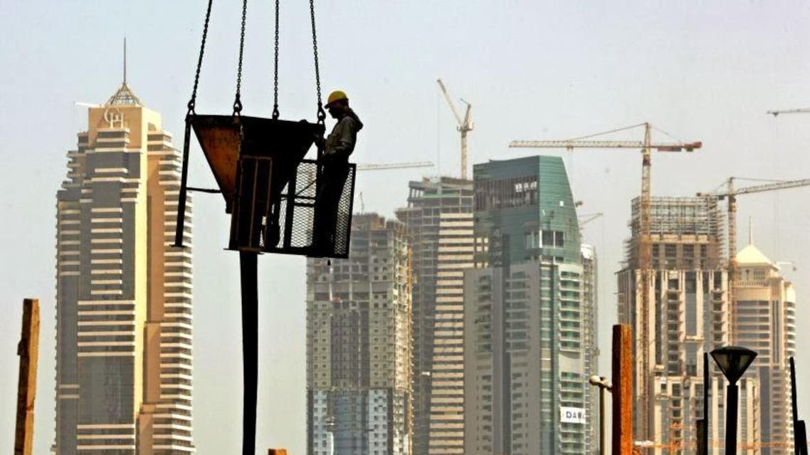 With a general view of Dubai Marina towers, a laborer holds a concrete bucket below a crane at a construction site in Dubai. (File photo: AP)