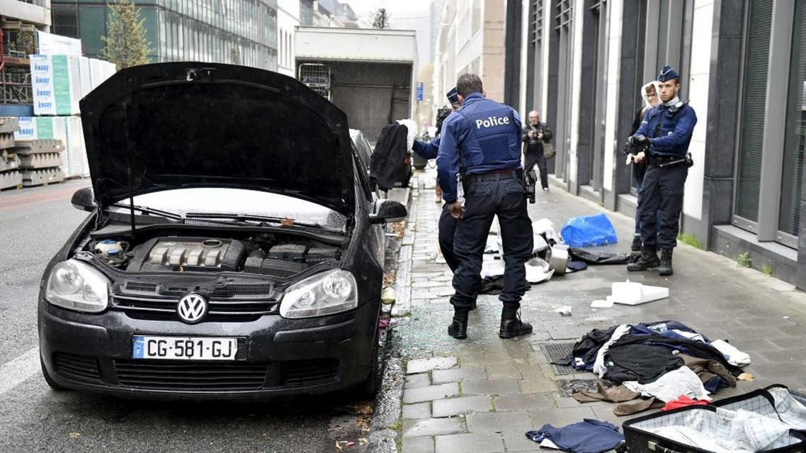Police officers check a suspected car during an alert in Brussels | Reuters