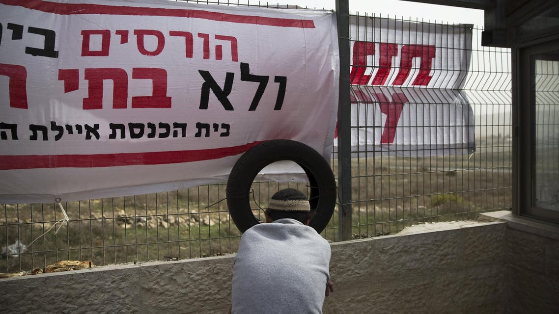 An Israeli youth sits near a tyre leaning against the fence of a synagogue during a protest against its planned demolishment in the Israeli settlement of Givat Zeev. (File photo: Reuters)