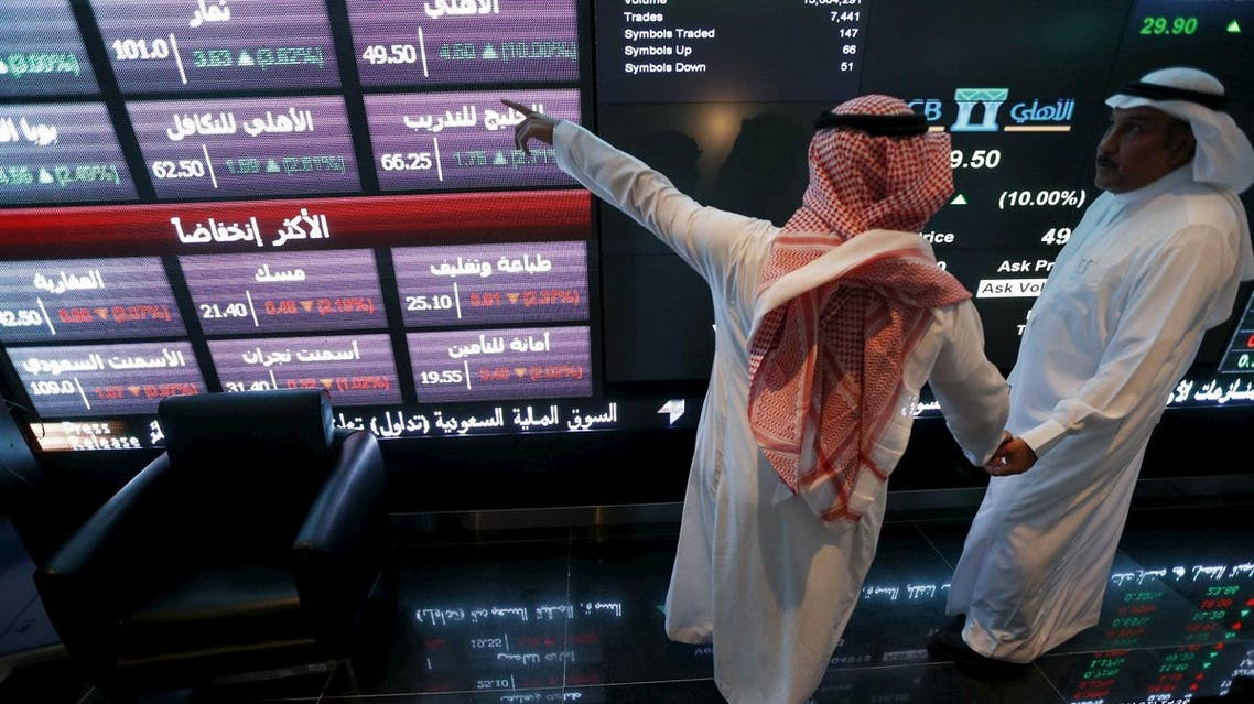 File photo of investors talking as they monitor screens displaying stock information at the Saudi Stock Exchange. (File photo: Reuters)
