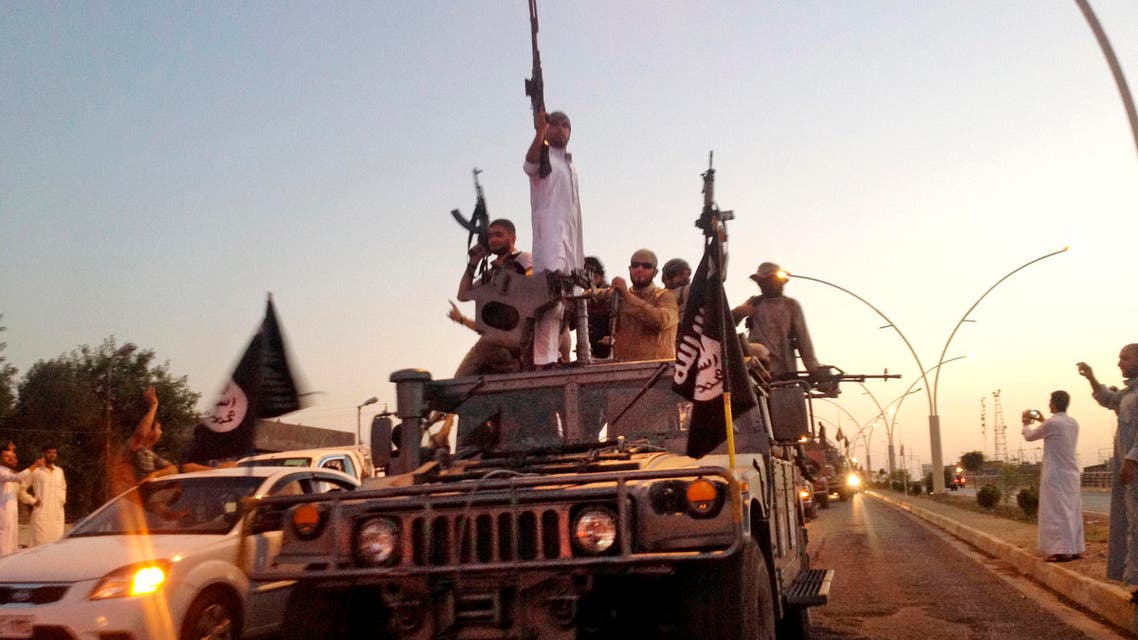FILE - In this Monday, June 23, 2014 photo, fighters from the Islamic State group parade in a commandeered Iraqi security forces armored vehicle down a main road at the northern city of Mosul, Iraq. (AP Photo, File)