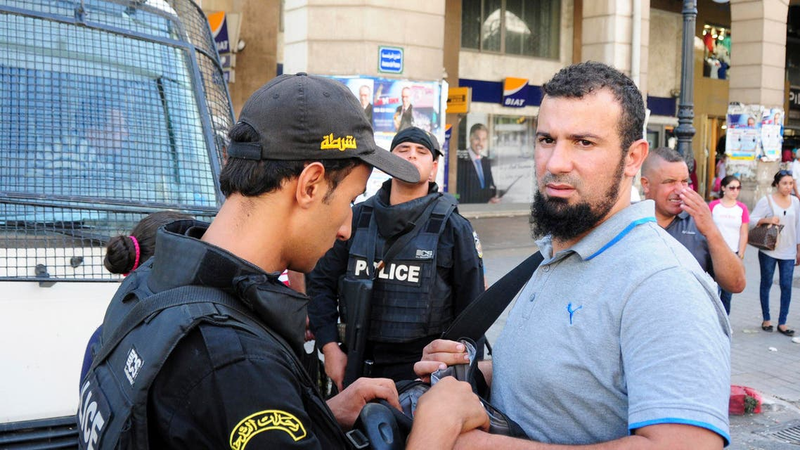 Tunisian police checks a demonstrator during a march under heavy security to protest a law offering amnesty for those accused of corruption, in Tunis, Tunisia, Saturday Sept. 12, 2015. The controversial draft law on economic reconciliation is a centerpiece of the new government's program and seeks to boost the economy by clearing cases against businessmen and civil servants accused of corruption. (AP Photo/Riadh Dridi)