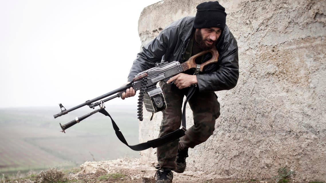 In this December 17, 2012 file photo, a Free Syrian Army fighter takes cover during fighting with the Syrian Army in Azaz, Syria.  AP