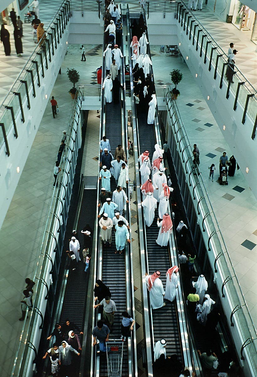 Qatari and foreigners share an escalator ride in one of Doha's many shopping malls. (File photo: AP)