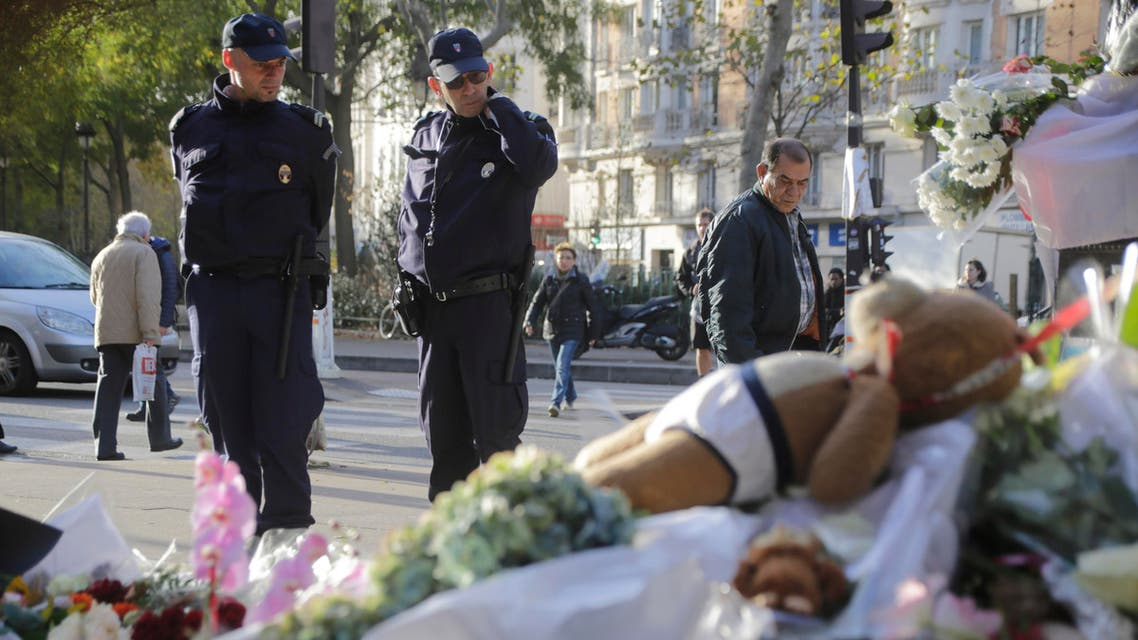 Policemen read messages which left at a makeshift memorial next to the Bataclan concert hall in Paris, France, Wednesday, Nov. 18, 2015. AP