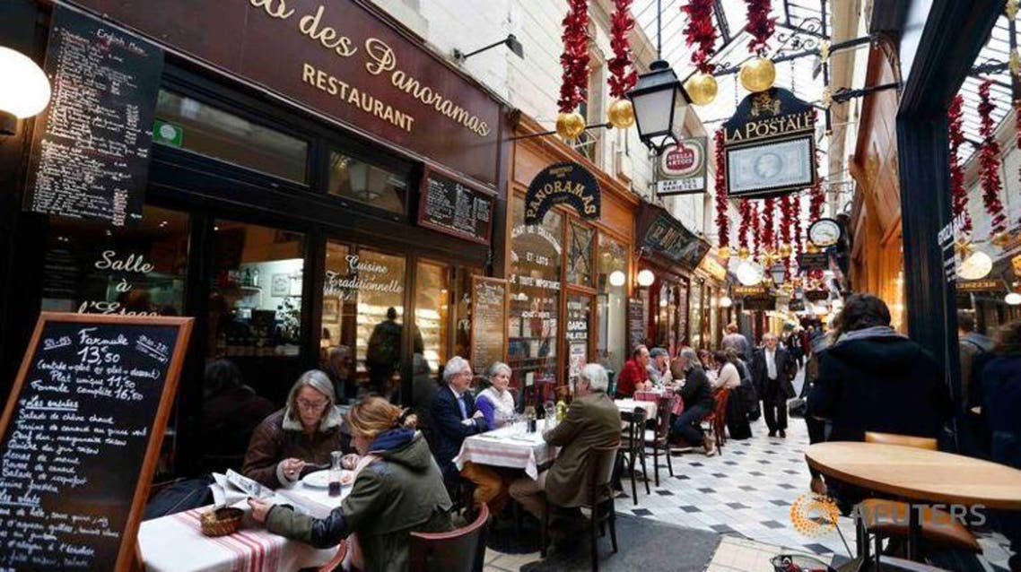 People sit at tables as they have lunch outside bistros in a covered passageway, the Passage des Panoramas, in Paris, France, November 17, 2015 | Reuters