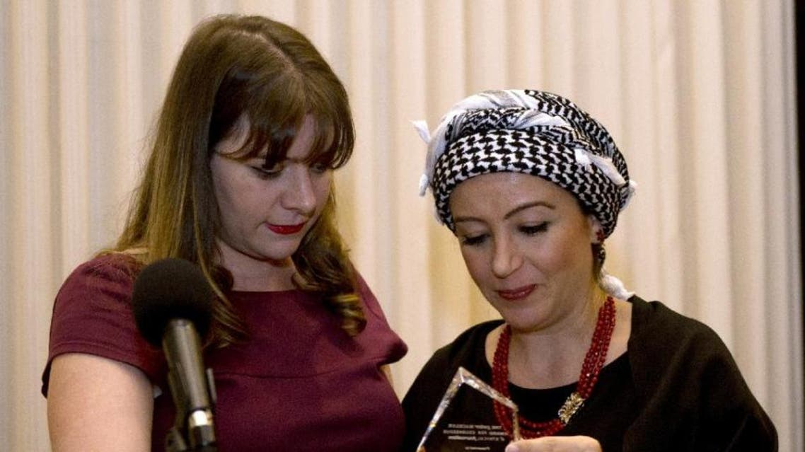 Syrian journalist Zaina Erhaim (R) receives the 2015 Peter Mackler award from Camille Mackler at the National Press Club in Washington, DC on October 22, 2015 | AFP