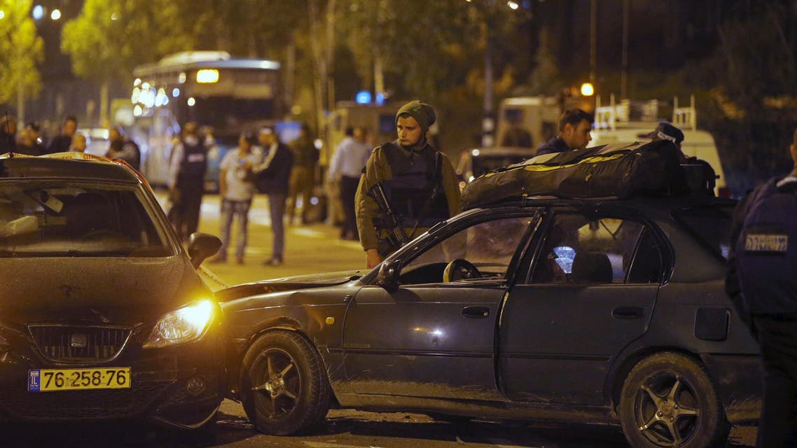 An Israeli soldier stands next to the car (R) of a Palestinian attacker at the scene close to the West Bank Jewish settlement of Alon Shvut November 19, 2015. REUTERS/Ronen Zvulun