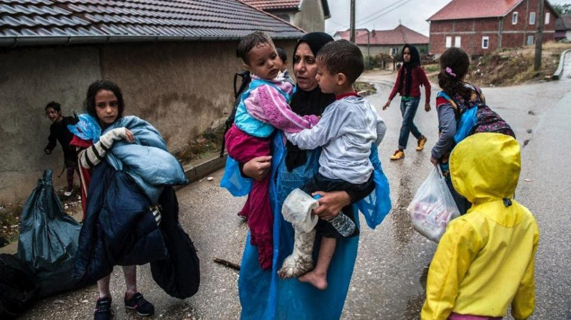 A migrant holds her children while walking through the Serbian town of Presevo, on September 10, 2015 (File photo: AFP)