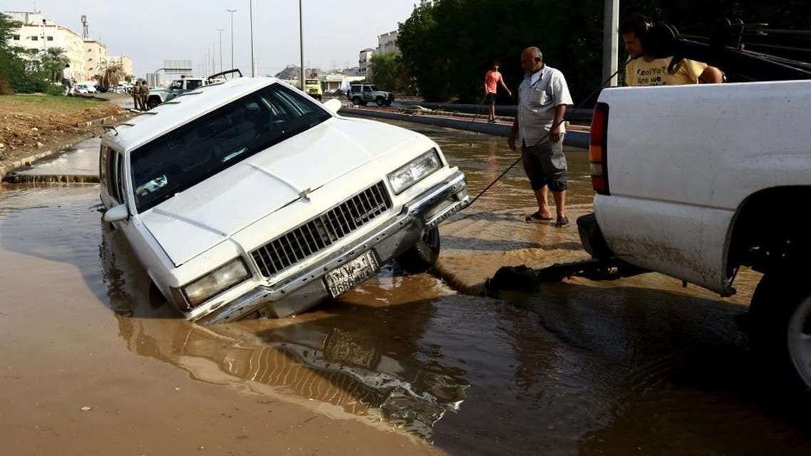 Men use a rope tied by a truck to tow a stuck car through a flooded street following heavy rain in Jeddah, Saudi Arabia November 17, 2015.REUTERS/Mohamed Al Hwaity