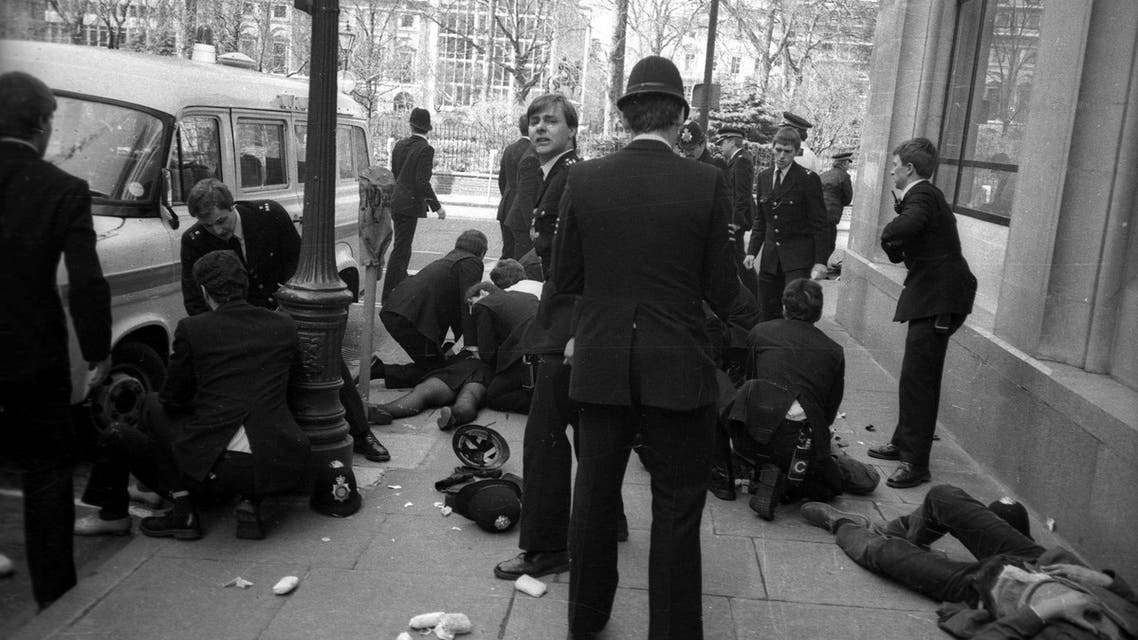 Police officers surround police constable Yvonne Fletcher after she was shot during a protest against Libyan leader Colonel Muammar Gaddafi in London, in this file photograph dated April 17, 1984. British police said they had arrested a Libyan man on November 19, 2015 for the 1984 murder of Fletcher who was shot dead outside the Libyan embassy in London. REUTERS/Clive Challis/files