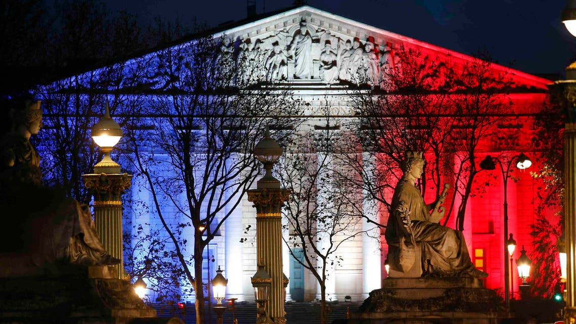 The National Assembly is lit with the blue, white and red colors of the French flag in Paris. (Reuters)