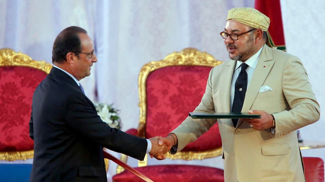 Morocco's King Mohammed VI, right, shakes hands with French President Francois Hollande following the signing of a convention between the two counties in the Moroccan port city of Tangiers, Sunday, Sept. 20, 2015. (AP)