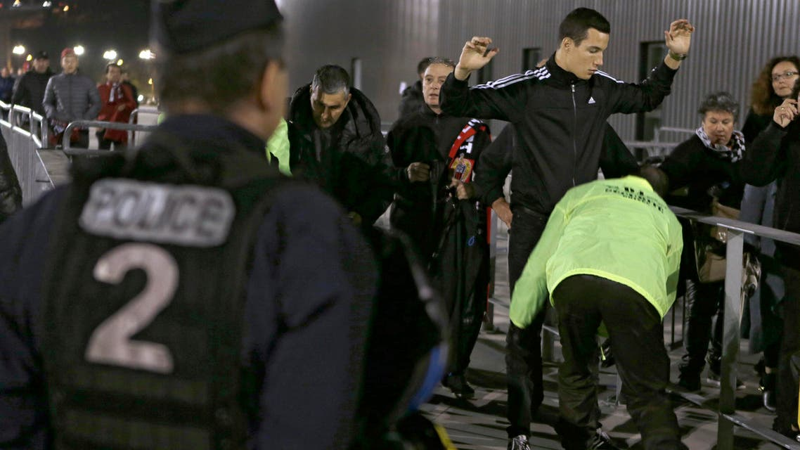 Supporters are checked by security at the entrance of the Nice stadium before the French League One soccer match between Nice and Lyon, Friday, Nov. 20, 2015
