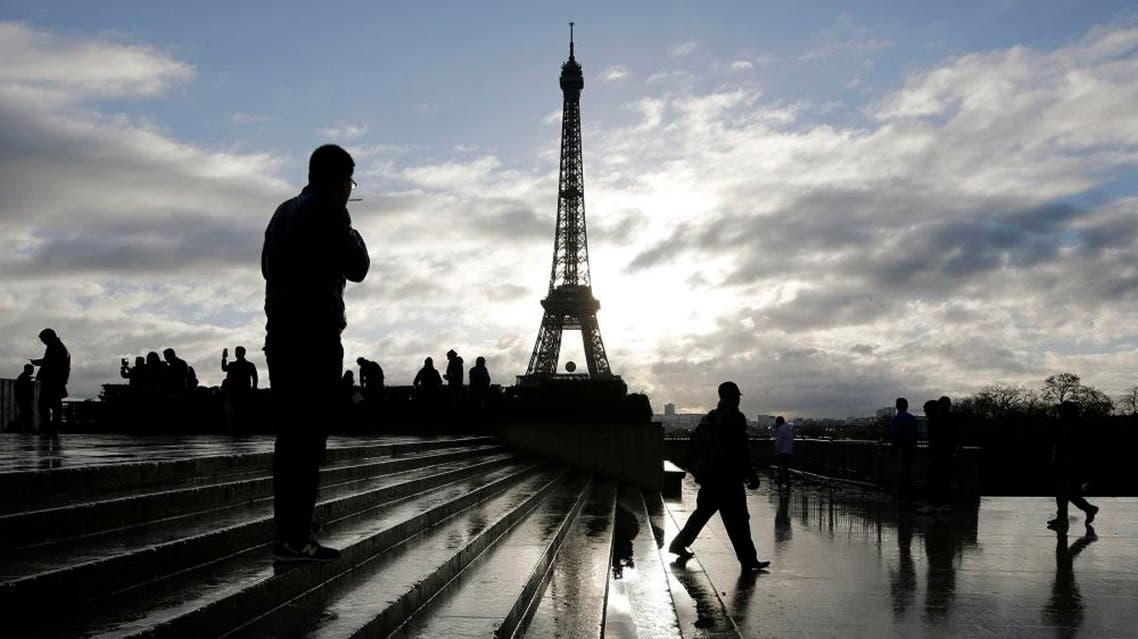 A man looks at the Eiffel tower from the Trocadero place a week after the start of the Paris attacks, in Paris, Saturday, Nov. 21, 2015. French President Francois Hollande will preside over a national ceremony on Nov. 27 honoring the victims of the deadliest attacks on France in decades. (AP Photo/Laurent Cipriani)