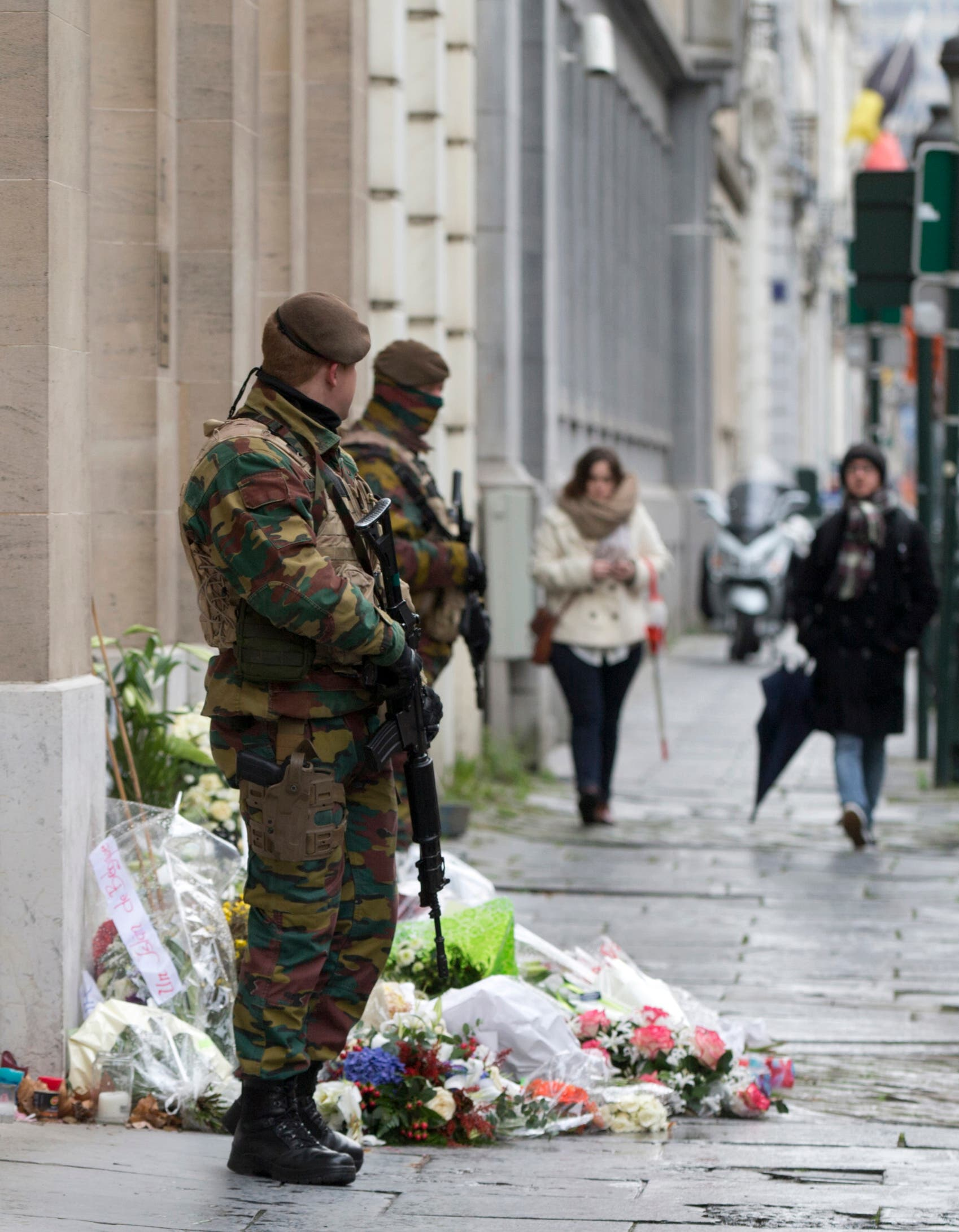 Belgian Army soldiers patrol next to flowers left outside of the French Consulates office in Brussels Saturday, Nov. 21, 2015. (AP)