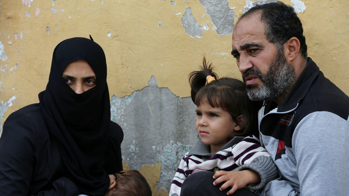 """In this picture taken on Friday, Oct. 23, 2015, Syrian refugee Anwar Ahmad Abdullah, 42, who fled from the central Syrian town of Palmyra from the Russian airstrikes, holds his daughter Yara, 3, as he sits next to his wife Hind, left, during an interview with The Associated Press at their unfurnished home, in the Turkish-Syrian border city of Reyhanli, southern Turkey. """"We had no intention to leave our country at all. But the Russian airstrikes made us leave Syria,"""" Abdullah's wife, Hind, said as her 10-month-old son Abdul-Muneim slept in her lap. She said Russian bombing was more intense and destructive than government strikes. (AP Photo/Hussein Malla)"""