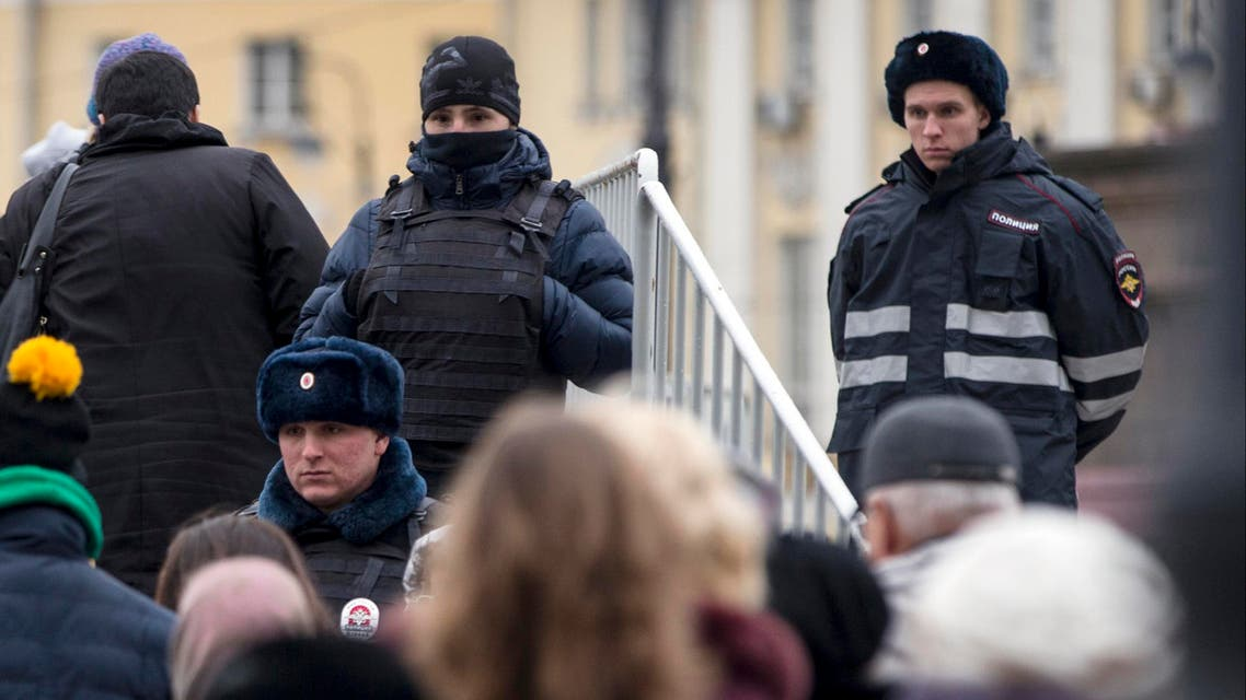 Russian police officers watch people as they line for an exhibition, in Manezh Square outside the Kremlin in Moscow, Russia, Friday, Nov. 20, 2015. In reaction to the recent attacks in France, Russian security forces across the country, are introducing additional measures to strengthen security. (AP Photo/Pavel Golovkin)