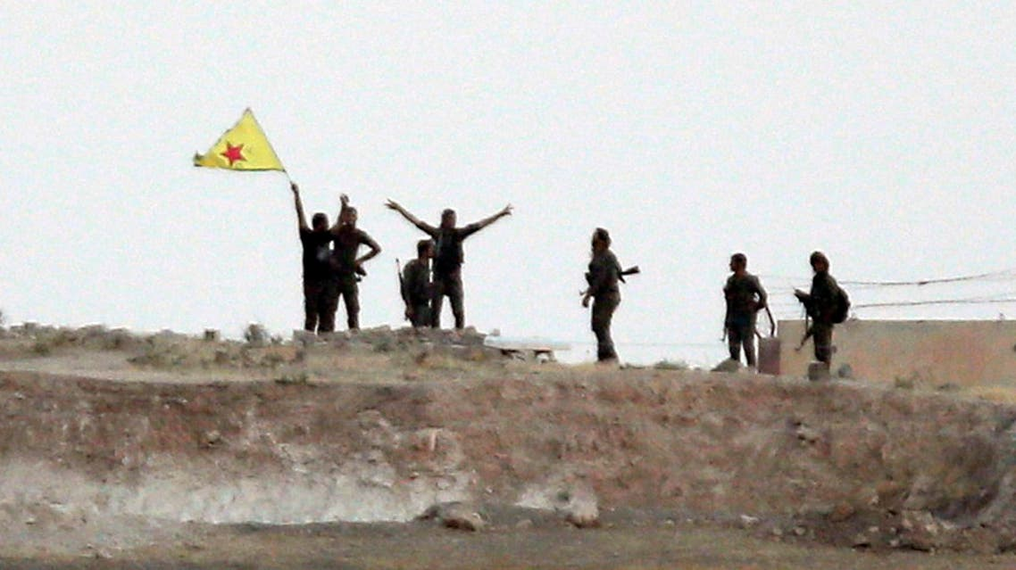 In this June 15, 2015 file photo taken from the Turkish side of the border between Turkey and Syria, in Akcakale, southeastern Turkey, Kurdish fighters with the YPG, wave their yellow flag in the outskirts of Tal Abyad, Syria. (AP)