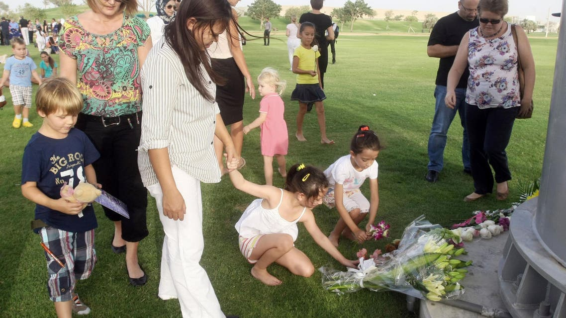 "Children place flowers during a memorial held at the ""Aspire Zone"" close to the scene where two-year-old New Zealand triplets perished in a massive fire that tore through a nursery at a Qatar shopping mall in Doha, Tuesday, May 29, 2012."