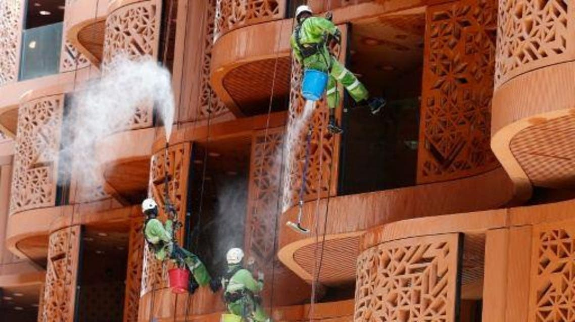 Workers clean the front of a building in Masdar City, on the outskirts of the rich Emirate of Abu Dhabi, on October 7, 2015. (AFP)