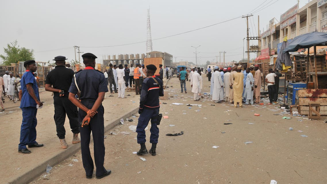 Security officers stand guard at the scene of an explosion at a mobile phone market in Kano, Nigeria. Wednesday Nov. 18, 2015. The suicide bomber exploded as truckers were tucking into dinner at the bustling marketplace where vendors urged them to buy sugar cane. At least 34 people were killed and another 80 wounded in Yola, a town packed with refugees from Nigeria's Islamic uprising, emergency officials said Wednesday. Later Wednesday, two more suicide bombers killed at least 15 people in the northern city of Kano and injured 53, according to police. (AP Photo/Muhammed Giginyu)