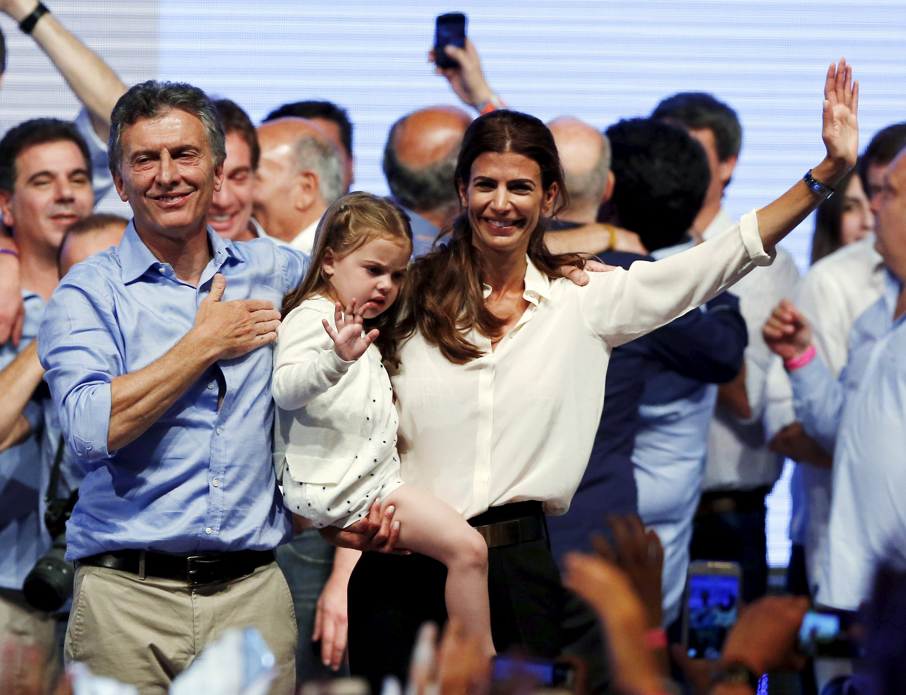Mauricio Macri, presidential candidate of the Cambiemos (Let's Change) coalition, his wife Juliana Awada and their daughter Antonia gesture to their supporters after the presidential election in Buenos Aires, Argentina, November 22, 2015. Conservative opposition candidate Macri comfortably won Argentina's presidential election on Sunday after promising business-friendly reforms to spur investment in the struggling economy. REUTERS/Ivan Alvarado TPX IMAGES OF THE DAY
