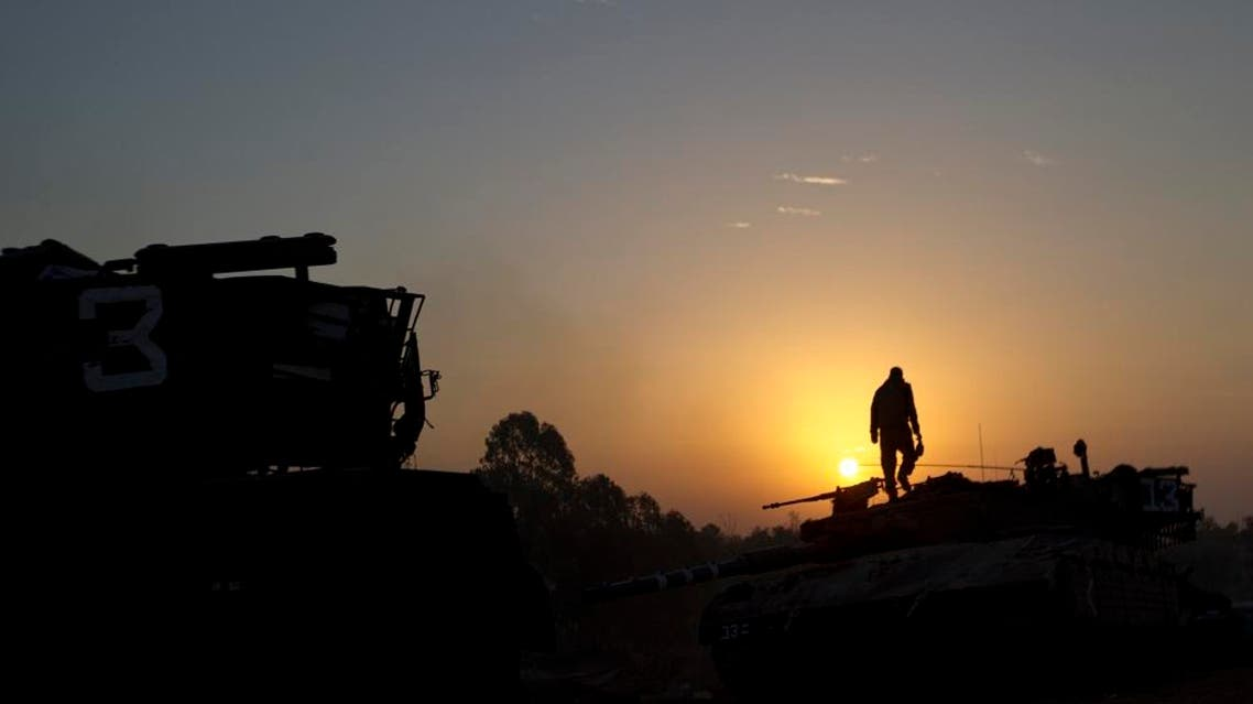 An Israeli soldier stands on top of a military vehicle as the sun rises in a staging area near the Israel Gaza Border, southern Israel (AP)