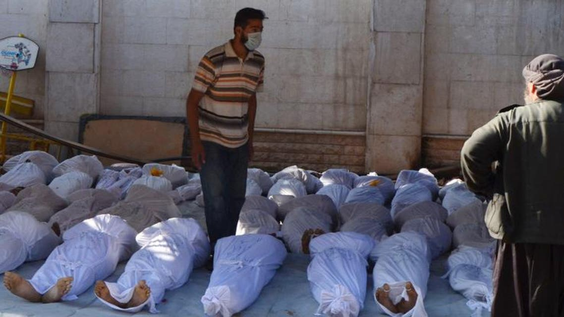 Syrian activists inspect the bodies of people they say were killed by nerve gas in the Ghouta region. (Reuters)