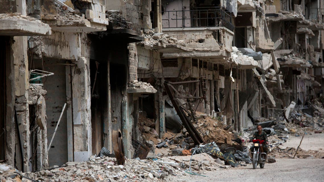 In this Thursday June 5, 2014 photo, a man rides a motorcycle in a devastated part of Homs, Syria. Syrian government forces retook the control of Homs in May 2014, after a three year battle with rebels. (AP Photo/Dusan Vranic)