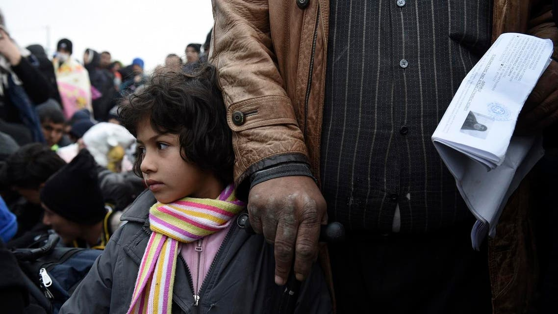 A Syrian girl with her father wait to be allowed by the Greek police to cross the borderline to Macedonia, near the village of Idomeni. (File photo: AP)
