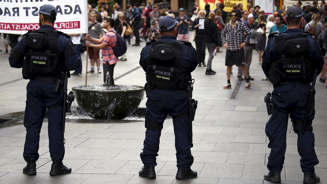 Police stand in front of anti-racism supporters during a rally in central Sydney, Australia, November 22, 2015.