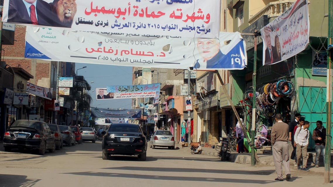 People and vehicles are seen under electoral banners ahead of the second round of parliamentary election, in Al Arish city. (File photo: Reuters)