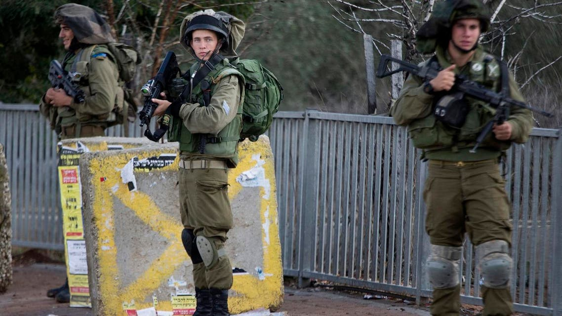 Israeli soldiers stand guard at a bus stop after near the Palestinian town of Nablus in the occupied West Bank. (File photo: AP)