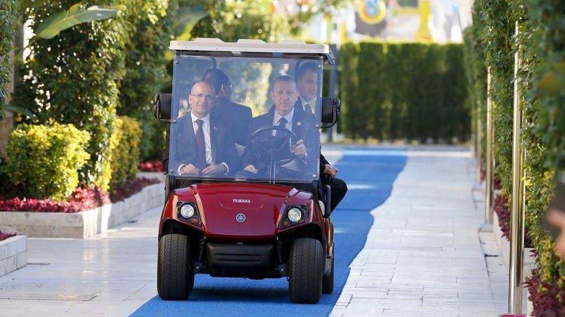 Turkey's President Tayyip Erdogan (R), accompanied by Finance Minister Mehmet Simsek (L), drives a buggy ahead of the G20 summit in Belek in the Mediterranean resort city of Antalya, Turkey, November 14, 2015. | Reuters