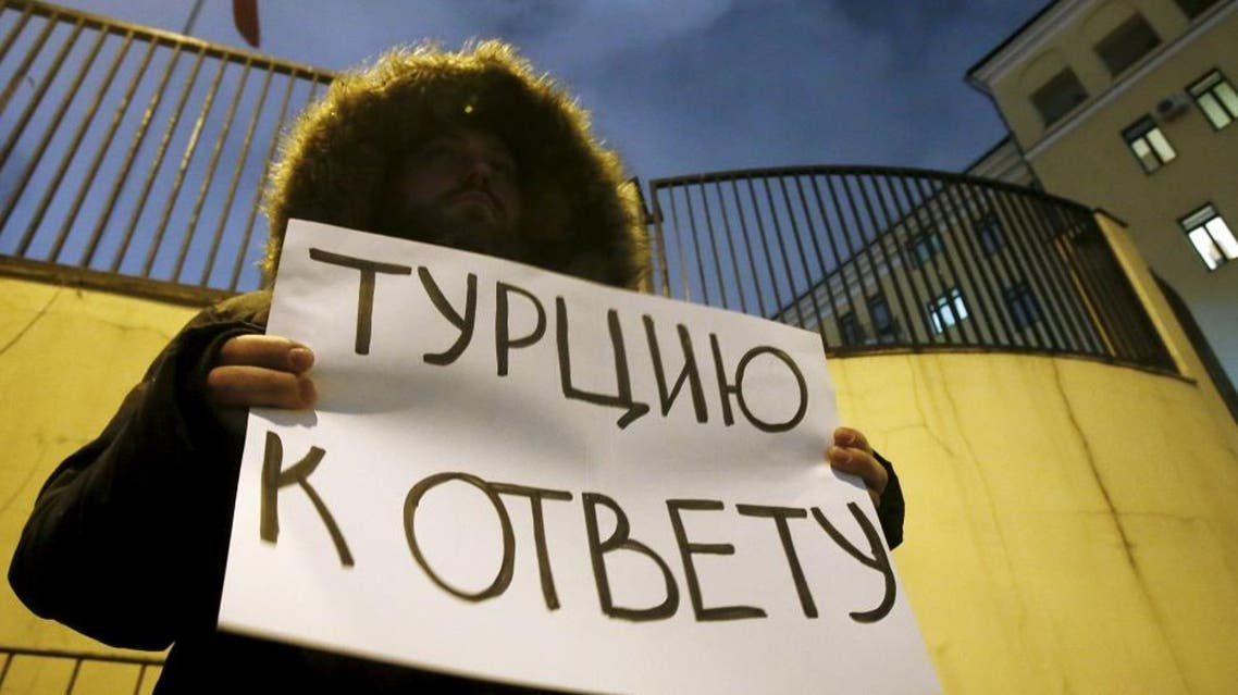 """An activist holds a placard that reads, """"Bring Turkey to account"""" to protest in reaction after a Russian war plane was shot down by Turkey, in front of the Turkish embassy in Moscow, Russia November 24, 2015. (File photo: Reuters)"""