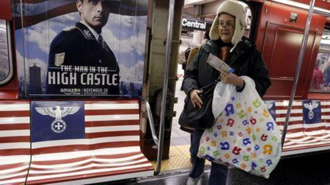 "Passengers board a 42nd Street Shuttle subway train, wrapped with advertising for the Amazon series ""The Man in the High Castle"" in Manhattan, New York. (Reuters)"
