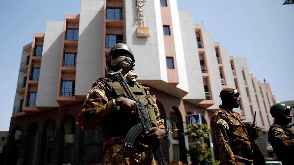 """Tight security surrounds Malian President Ibrahim Boubacar Keita as he visits the Radisson Blu hotel in Bamako, Mali, Saturday, Nov. 21, 2015. Malian security forces were hunting """"more than three"""" suspects after a brazen assault on a luxury hotel in the capital that killed 20 people plus two assailants, an army commander said Saturday. (AP Photo/Jerome Delay)"""