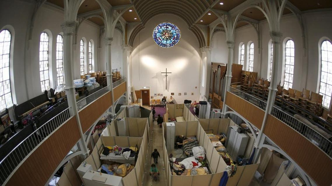Beds for migrants, separated by impromptu partition screens, are set up inside a Protestant church in Oberhausen, Germany, October 30, 2015. Up to 140 refugees are landing in Oberhausen every week, forcing authorities to come up with new locations to house them. City officials say they had little choice but to use the church. In early November, workers removed the altar and dozens of chairs, replacing them with metal beds, which are separated by makeshift partitions to give the church's new residents a semblance of privacy. Picture taken October 30, 2015. To match story EUROPE-MIGRANTS/GERMANY-CHURCH REUTERS/Ina Fassbender TPX IMAGES OF THE DAY