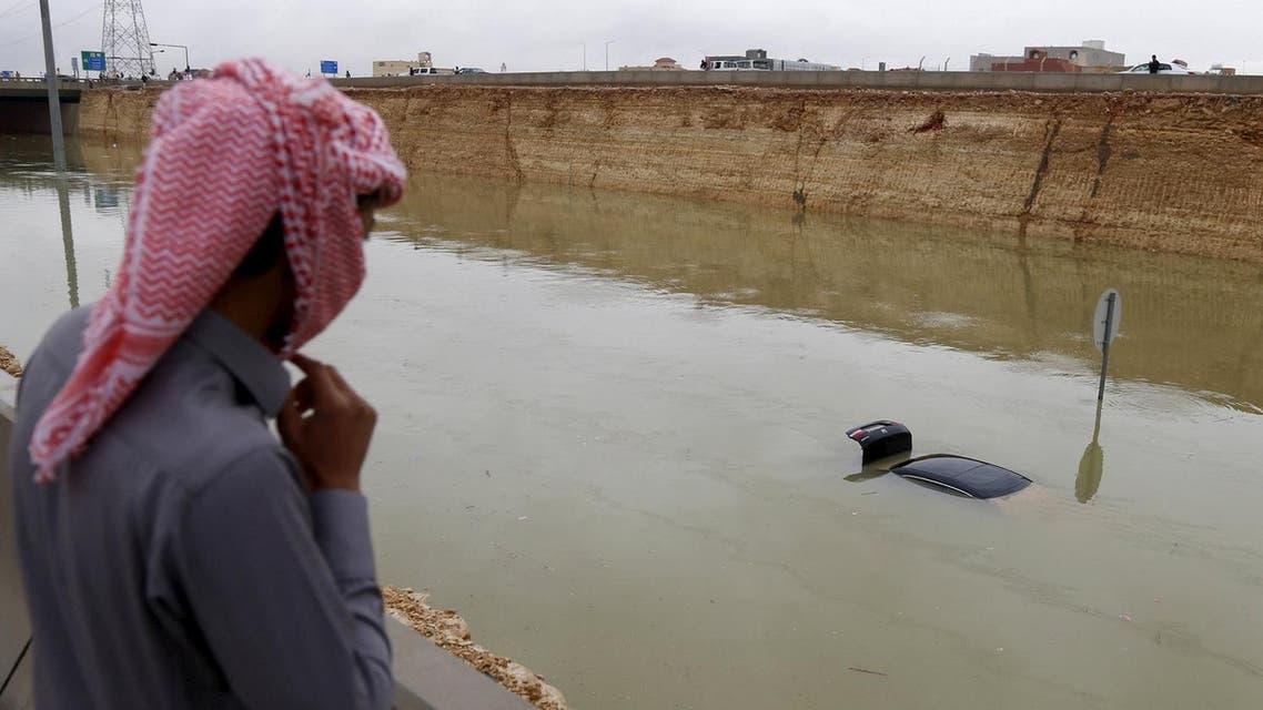 A Saudi man watches a car, submerged in flodd waters, following heavy rain in Riyadh. (Reuters)