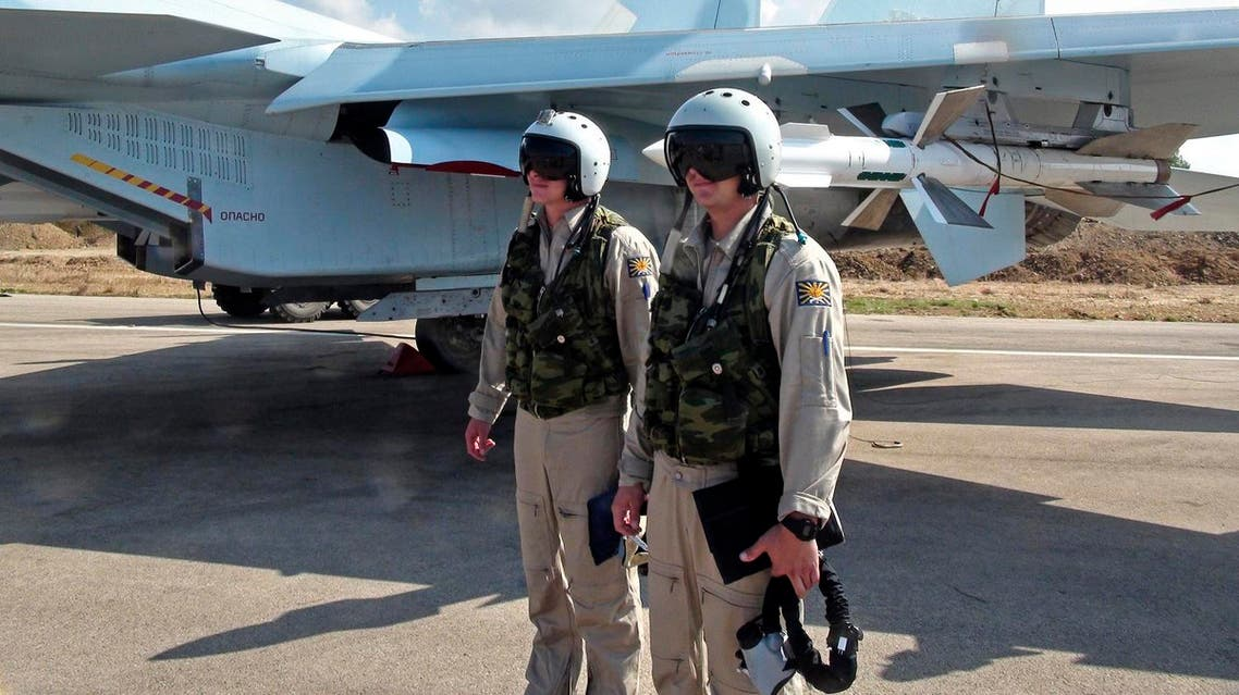 Russian pilots stand outside their Su-30 jet fighter, armed with air-to-air missiles, before a take off at Hmeimim airbase in Syria. (File photo: AP)