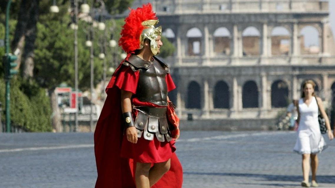 A man wearing a Roman centurion costume walks along an almost deserted Via dei Fori Imperiali avenue, which leads to Rome's Colosseum, background, Sunday, July 29, 2007 | AP