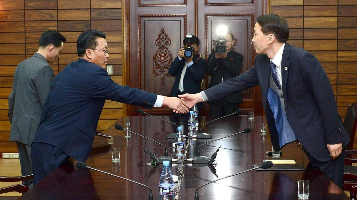 South Korean chief delegate Kim Ki-Woong shakes hands with his North Korean counterpart Hwang Chol during their meeting at the truce village of Panmunjom