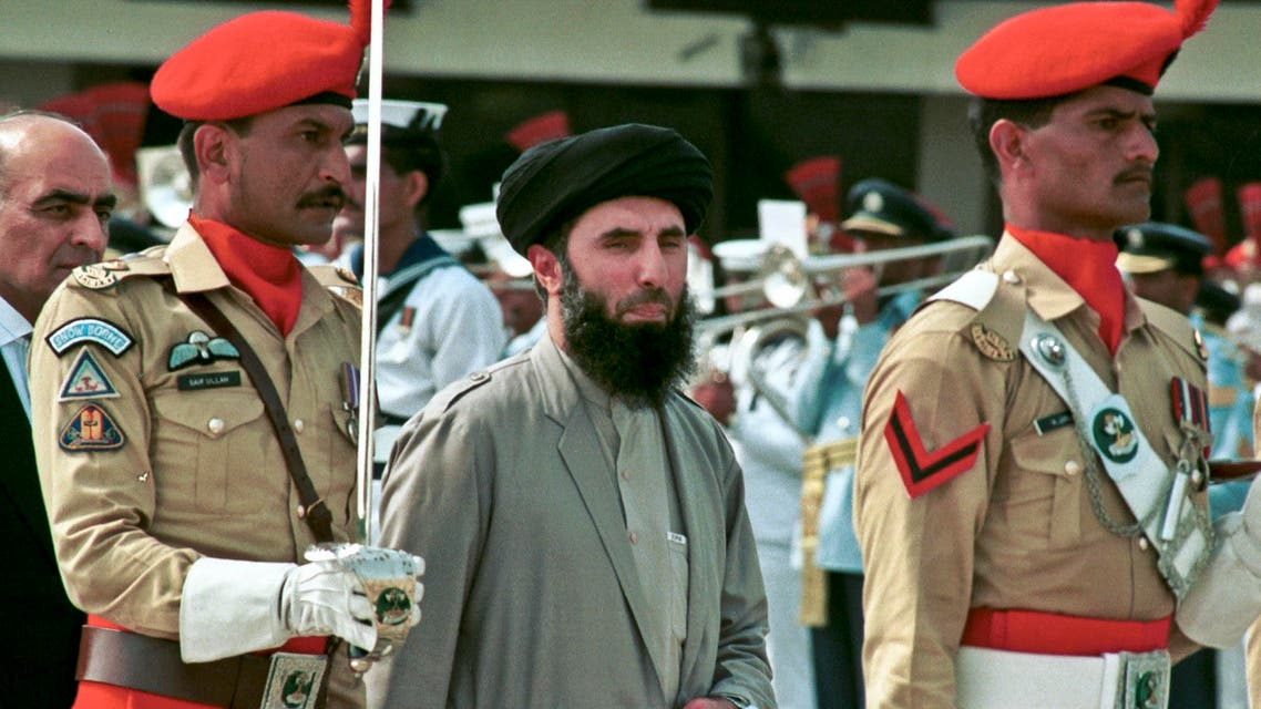 In this Wednesday, June 26, 1996 file photo, Gulbuddin Hekmatyar, center, passes in front of an honor guard in the Afghan capital of Kabul, Afghanistan.