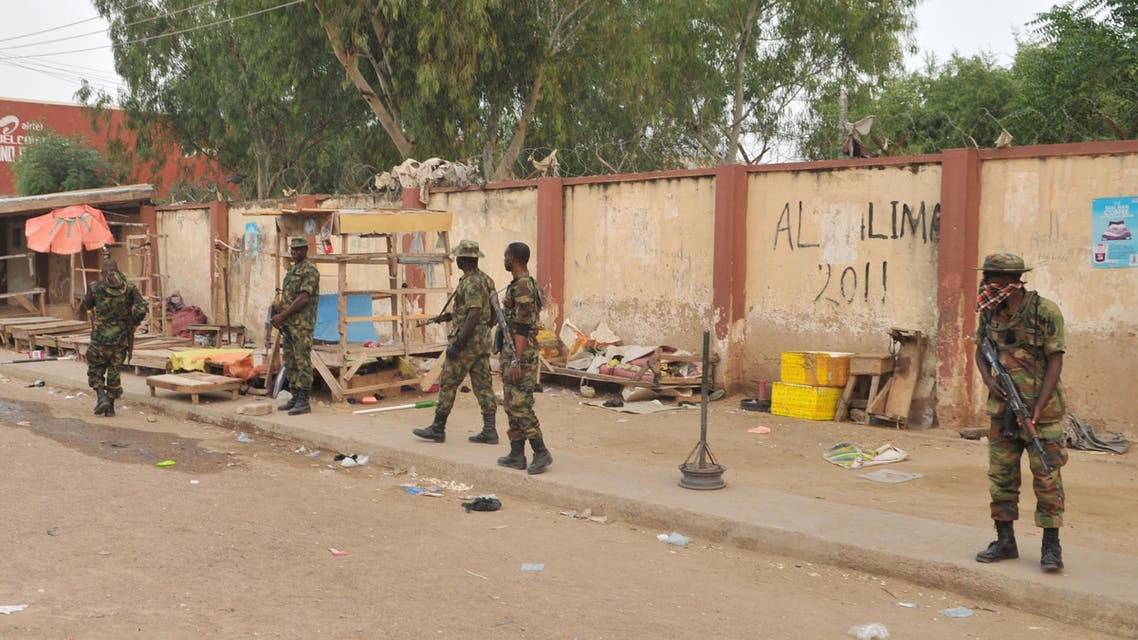 Soldiers stand guards at the scene of an explosion at a market in Kano, Nigeria. Wednesday Nov. 18, 2015. (AP)