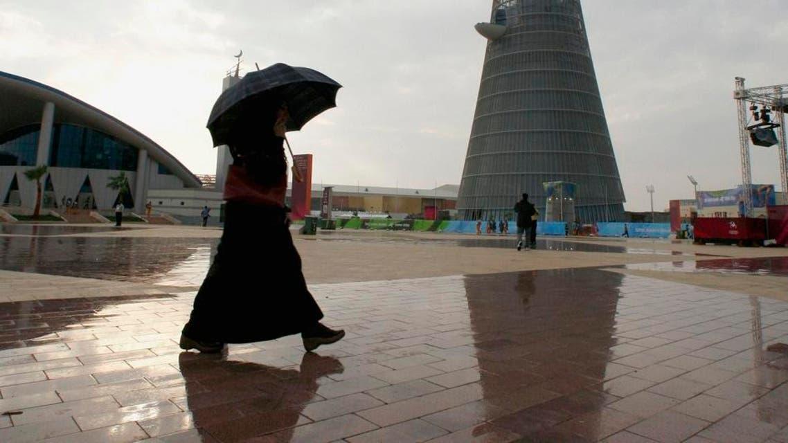 A Qatari woman walks in the rain near the Khalifa Stadium before the Asian Games Opening ceremony in Doha. (File photo: Reuters, 2006)